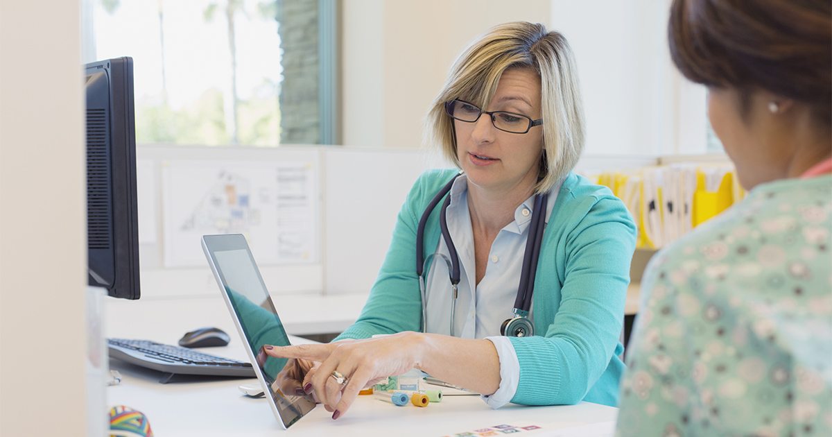 health care professionals discussing information on a tablet screen
