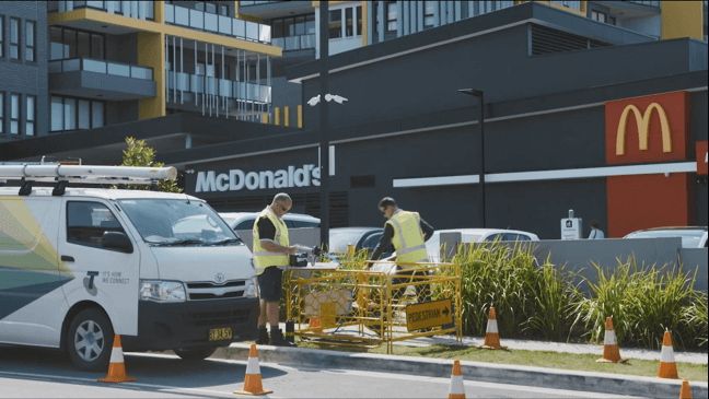 Telstra technicians working outside Mcdonalds Restaurant