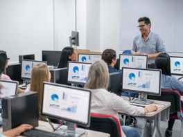 man teaching to classroom of students on computers