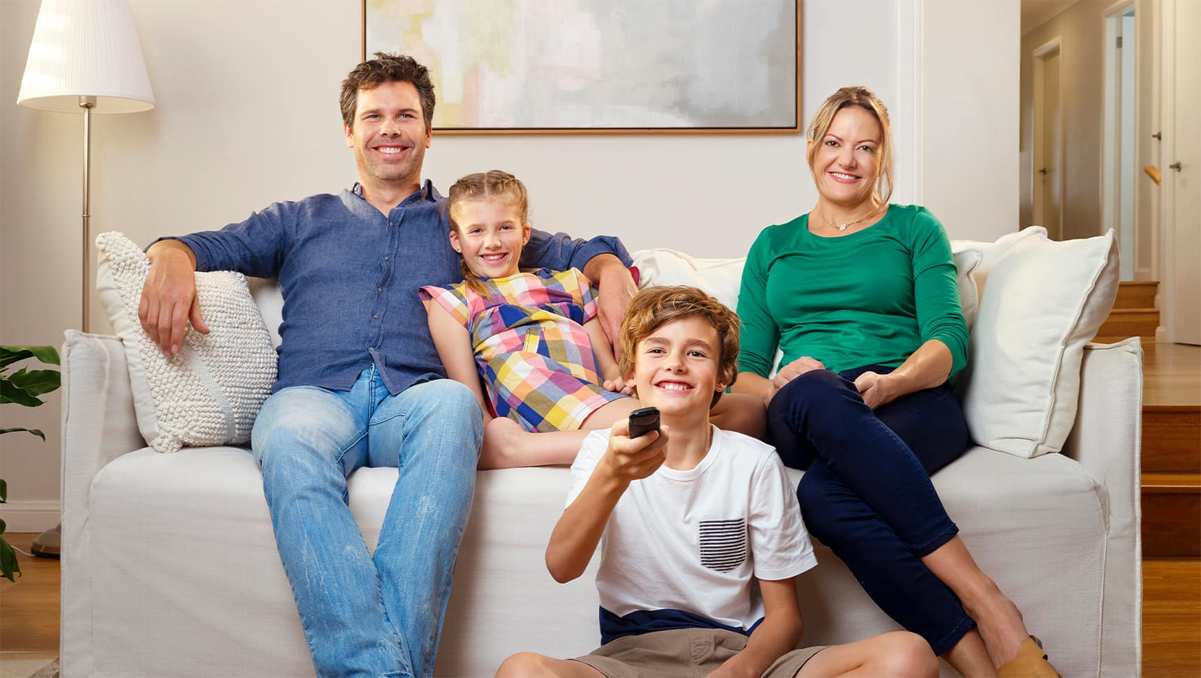 Young family on the couch watching the latest release movies with Telstra entertainment