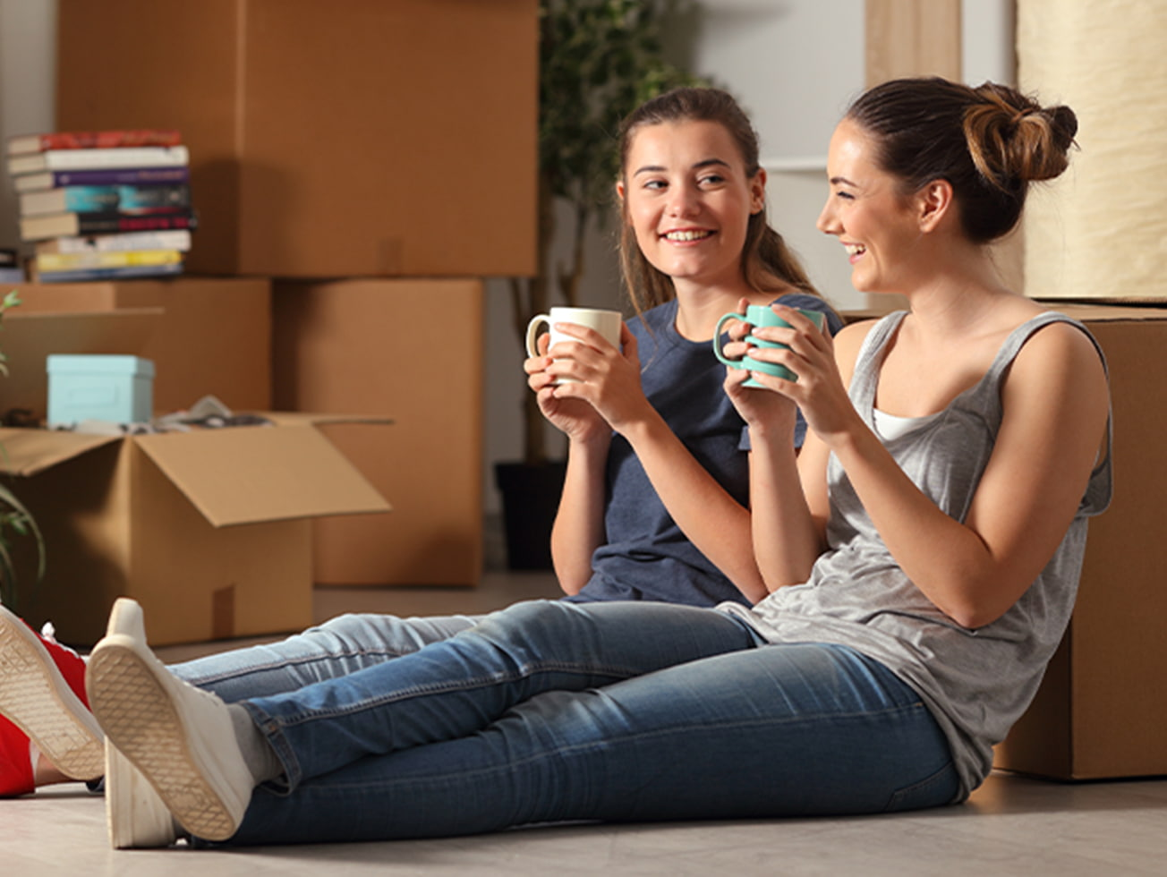 Two young women unpacking boxes after moving home and internet