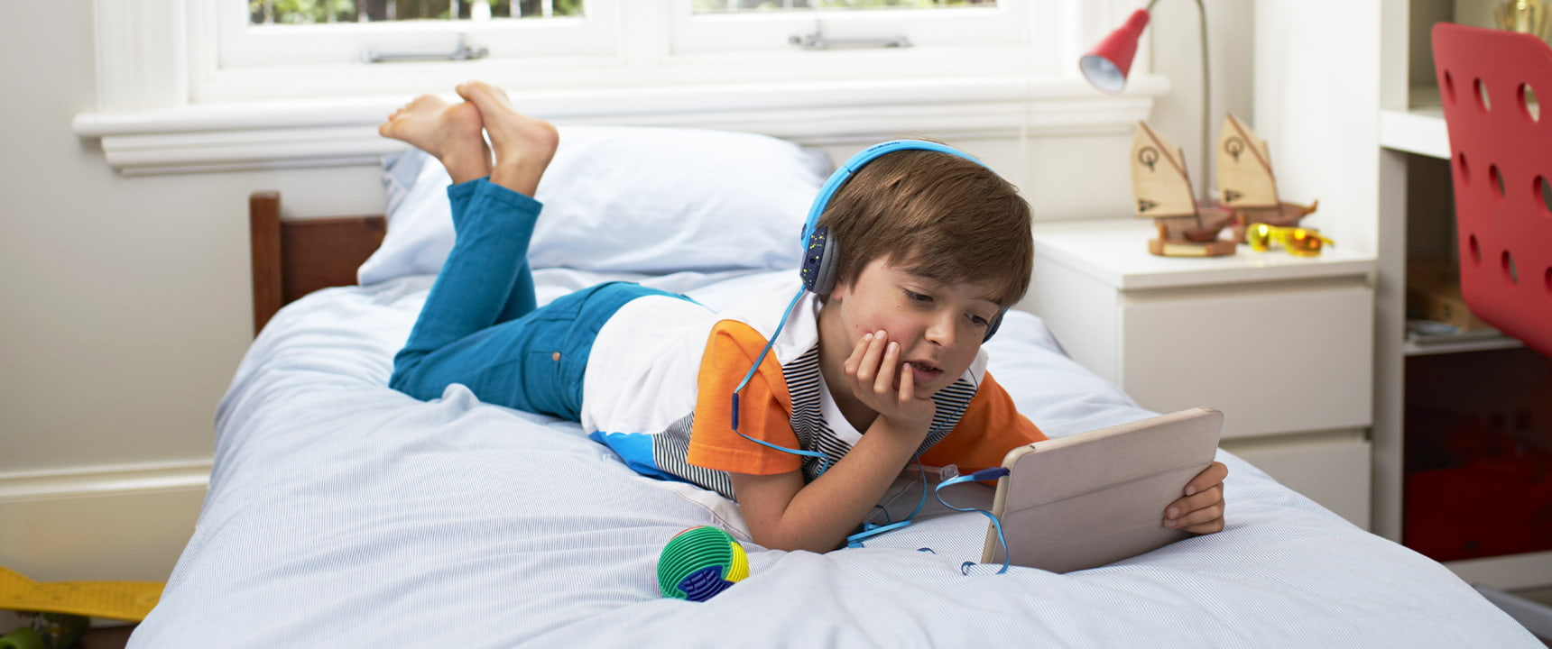 Young boy on his bed watches his iPad with headphones using Telstra cable internet