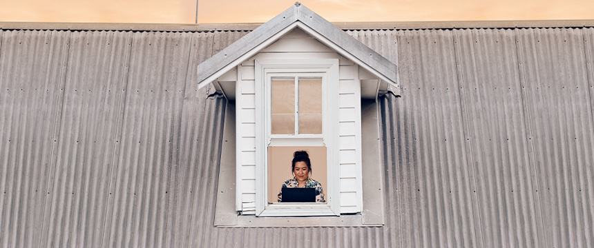 Woman on laptop next to the window trying to get a wi-fi signal
