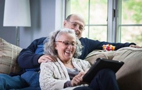couple on the couch looking at tablet device